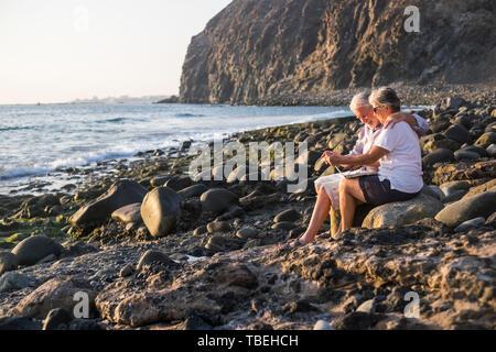 Happy active young senior personnes profitez de la plage de pierres et de travailler ensemble sur un ordinateur portable connecté à la retraite pour le mode de vie moderne - mat Banque D'Images