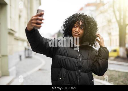 Cheerful young African woman wearing coat la marche à l'extérieur, en prenant un selfies