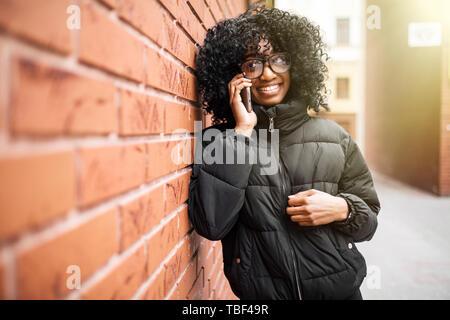 Portrait de jolie femme noire de fond urbain en parlant au téléphone Banque D'Images
