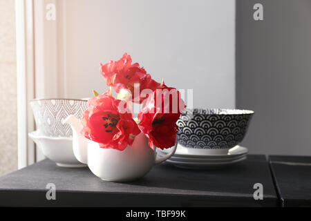 Théière avec de belles fleurs et de la vaisselle sur la table près de window