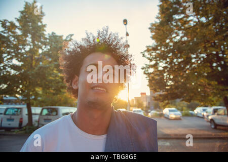 Hipster urbain happy smiling young man using smart phone. African American teenager holding mobile smartphone sur le coucher du soleil avec des reflets Banque D'Images