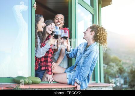 Young Friends toasting with red wine party au coucher du soleil sur le patio de grand standing - les gens heureux s'amusant sur un week-end journée ensoleillée sur terrasse Banque D'Images