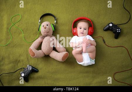 Adorable bébé garçon avec des ours en peluche, de casques et de joypads,ou joysticks plaid doux
