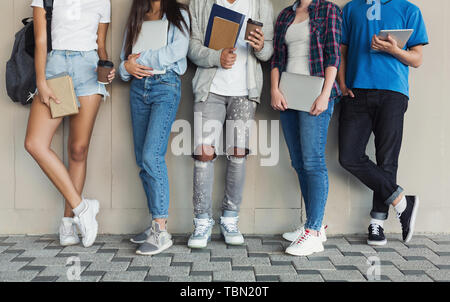 Les adolescents au campus permanent wall, appareils et livres Banque D'Images