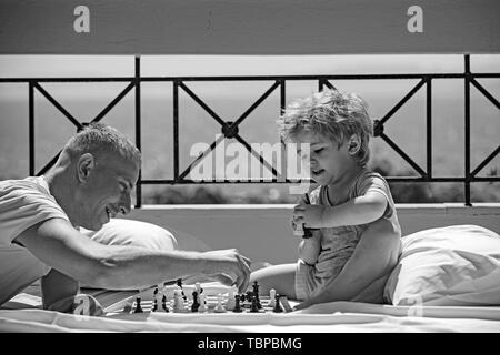 Enseignement l'homme garçon les règles du jeu d'échecs - jouant sur le plancher de balcon. Banque D'Images