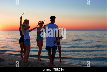 Happy smiling friends tournant à la plage avec des bougies scintillantes Banque D'Images