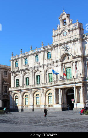 Catane, Sicile, Italie - 10 Avril 2019: Amazing face avant à l'extérieur de l'édifice historique de l'Université de Catane capturé sur une photographie verticale avec les gens marcher sur la place du centre. Banque D'Images