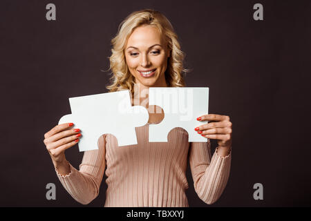 Happy blonde woman connexion jigsaw pieces isolated on black Banque D'Images