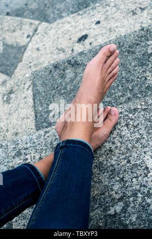 Libre d'un jeune homme de race blanche, vêtu d'un pantalon en jean, de repos nu assis sur un escalier dans la rue Banque D'Images