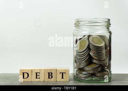 Planification de la collecte d'argent pour payer les dettes en concept. Dans un bol en verre de pièces avec une cale en bois sur bois tableau avec fond blanc. La démonstration Banque D'Images