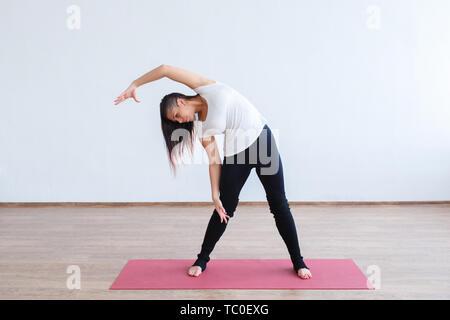 Tourné sur toute la longueur de la fit young woman doing stretching entraînement. Modèle de remise en forme de l'exercice en plein air. matin Banque D'Images