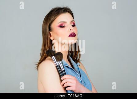 Attractive Woman applying makeup brush. Maquillage professionnel fournitures. Maquilleur concept. L'accent sur la féminité. Appliquer fille ombres à paupières. À la bonne et très confiant. Soins de la peau cosmétiques. Banque D'Images