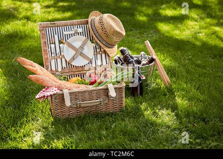 L'été de style vintage pique-nique végétarien dans un panier en osier avec de vieux chapeau de paille et le refroidisseur de bouteilles de bière sur le côté sur l'herbe verte et luxuriante en plein air Banque D'Images