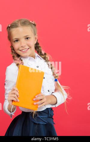 Si la connaissance dont vous avez besoin, vous devez lire. Cute little child holding livre sur fond rouge, petite fille avec réserve la connaissance dans les mains. Jour des connaissances ou le 1 septembre. L'accumulation de connaissances, l'espace de copie. Banque D'Images