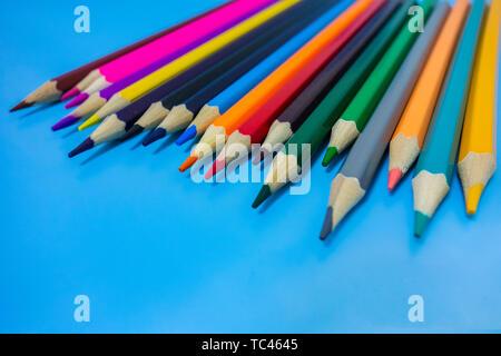 Un crayon de couleur sont soigneusement disposées dans un fond bleu