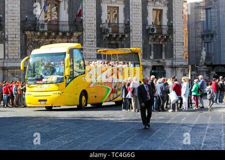 Catane, Sicile, Italie - 10 Avril 2019: Jaune hop on hop off bus de tourisme à Piazza Duomo Square avec un groupe de touristes. La place principale dans le centre-ville est une attraction touristique populaire. Banque D'Images