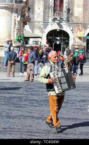 Catane, Sicile, Italie - 10 Avril 2019: l'homme gris âgés jouant sur l'accordéon busker Piazza Duomo square de la vieille ville. Performance de rue divertissant pour le pourboire. Banque D'Images
