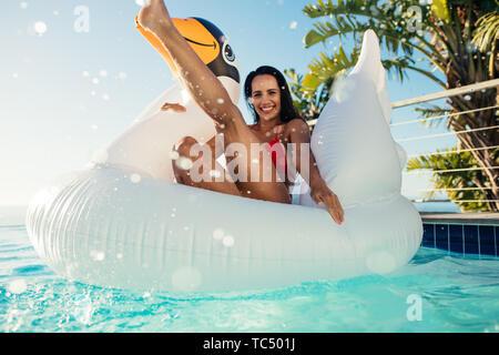 Belle jeune femme en bikini les projections d'eau avec ses pieds tout en étant assis sur la piscine gonflable dans Swan. Femme jouant sur Jouet flottant dans la piscine Banque D'Images