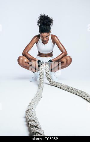 Femme africaine à épuisé après l'entraînement physique intense sur fond blanc. Jeune femme se reposant après l'élaboration avec bataille des cordes. Banque D'Images