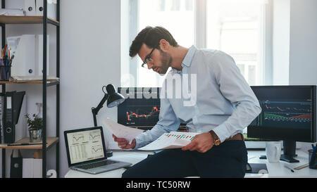 Dure journée de travail. Jeune commerçant réussi ou businessman dans l'usure formelle et les lunettes assis à un bureau moderne contre l'écran de l'ordinateur avec les graphiques et la lecture du rapport du marché. Courtier en valeurs. Le marché de Forex. Concept commercial Banque D'Images