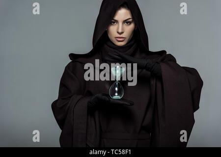 Vue avant de la femme en costume de mort holding sand réveil isolé sur gray Banque D'Images