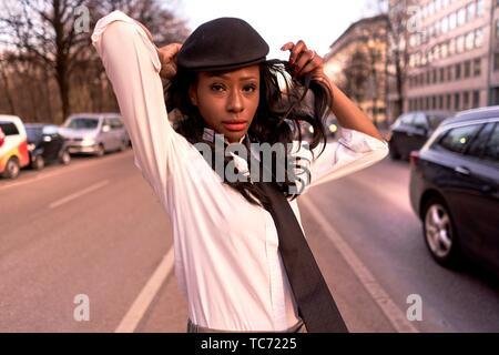 Femme élégante soirée dans la lumière du soleil dans la rue à côté de trafic, le port de vêtements rétro, regard d'affaires de l'Afrique, l'ascendance, l'Angolais dans la ville de Munich, Allemagne. Banque D'Images