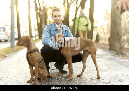 L'homme avec les chiens tenus en laisse en ville, à Munich, Allemagne. Banque D'Images