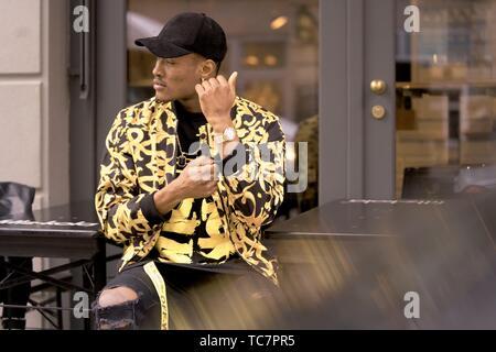 L'homme élégant de porter une montre-bracelet et de la mode, vêtements de réglage individuel, assis à l'extérieur en ville, à Munich, Allemagne Banque D'Images