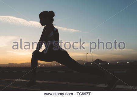 Jeune femme étonnante dans sporstwear s'étendant sur route sur fond coucher de soleil. Silhouette de belle figure, d'un mode de vie actif et d'entraînement dans l'été, profiter du sport, yoga, travailleurs sporstwoman Banque D'Images