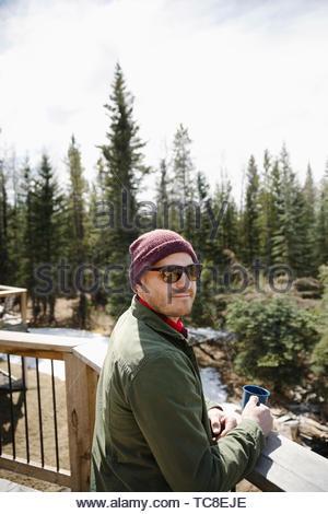 Portrait homme confiant boire du café sur le balcon bien exposé donnant sur woods Banque D'Images