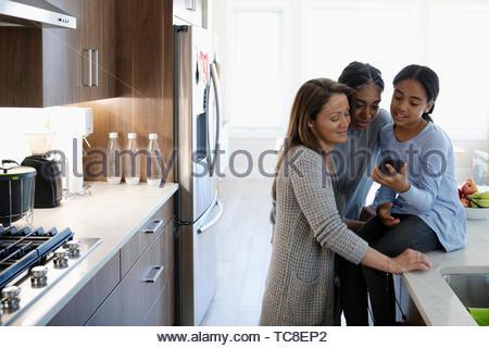 La mère et les filles à l'aide de smart phone in kitchen Banque D'Images