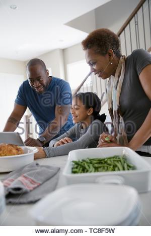 Multi-generation family with digital tablet à préparer le dîner dans la cuisine Banque D'Images