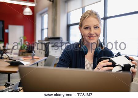 Portrait confiant computer programmer avec simulateur de réalité virtuelle de travail lunettes at laptop in office Banque D'Images