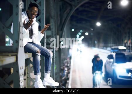 Jeune homme assis sur la construction métallique du pont, pont Hacker Hackerbrücke, la nuit dans la ville, à côté de rue, à Munich, Allemagne Banque D'Images