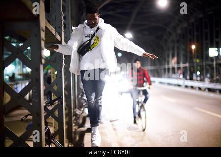 Jeune homme en équilibre sur la construction métallique du pont, pont Hacker Hackerbrücke, la nuit dans la ville, à côté de rue, location chauffeur, à Munich, Allemagne