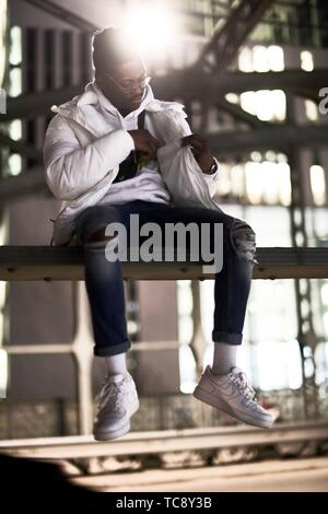 Jeune homme africain assis sur metal construction de pont, pont, Hacker, Hackerbrücke en ville la nuit, vérification à l'intérieur poche de veste, dans Banque D'Images