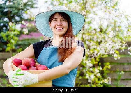 Image of smiling woman in hat avec fort avec des pommes dans le jardin par jour Banque D'Images