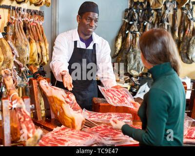 Poli vendeur travaillant derrière un comptoir dans une boucherie, jamon coupe pour female customer Banque D'Images