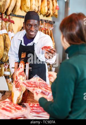 Poli vendeur travaillant derrière un comptoir à une boucherie, découpage jamon pour female customer Banque D'Images