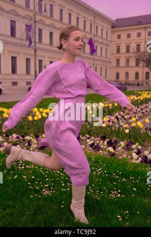 Mode femme tournant dans le parc en face de l'architecture riche, portant robe rose, la féminité aristocratique, printemps, à Munich, Allemagne Banque D'Images