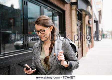Sac à dos femme avec l'aide de smart phone sur trottoir urbain Banque D'Images
