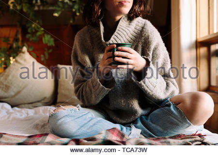 Serene woman relaxing with coffee on bed Banque D'Images