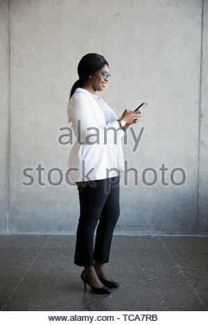 Smiling young businesswoman using smart phone Banque D'Images