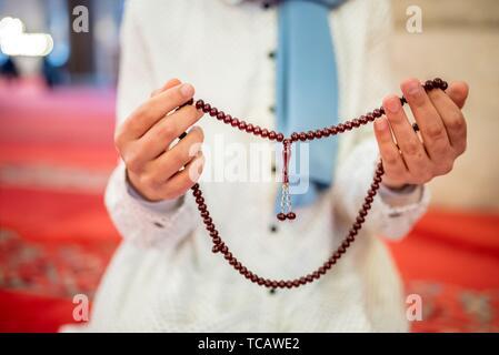 Vue rapprochée d'une femme musulmane dans les mains tout en maintenant l'hijab chapelet avec ses mains et en priant. Prier Religion concept.