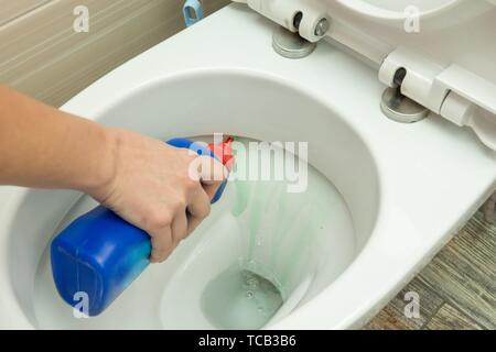 La main met un détergent liquide sous le bord de la cuvette des toilettes. Banque D'Images