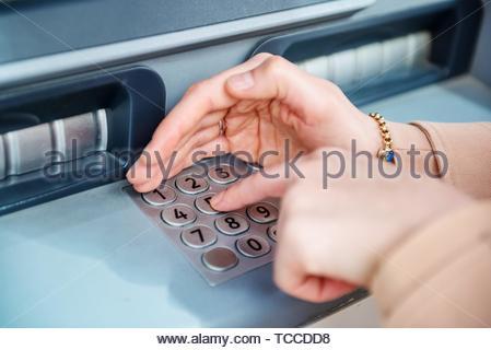 Carte de crédit entre les mains femme NIP au guichet automatique. Cash terminal ATM. Banque D'Images