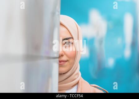 Belle femme musulmane en foulard et des vêtements modernes à la mode se cache la moitié de visage au mur avec fond bleu.