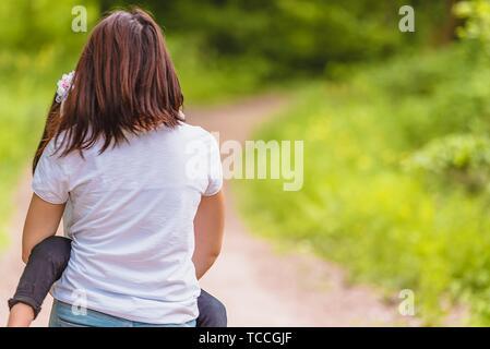 Jeune mère détient, elle épouse sa petite fille dans la forêt. Mère et fille heureux moments avec amour et émotion naturelle. Photo de mère et fille Banque D'Images