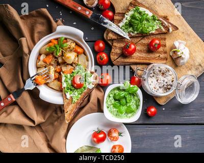 Vue de dessus les pommes de terre avec le poulet et les légumes, des sandwiches au fromage et tomates cerises sur un fond de bois sombre. Banque D'Images
