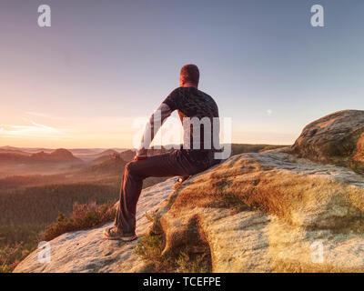 Flare. Défaut de l'objectif fort de réflexions. L'homme dans les vêtements de sport est assis sur le bord de la falaise et à la recherche à misty valle